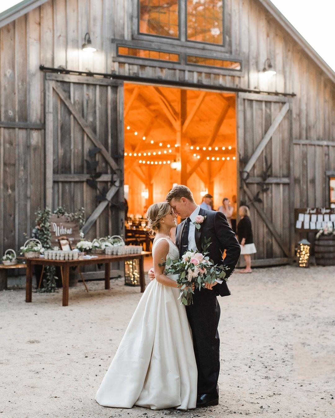 couple in front of barn glowing with light during their wedding reception
