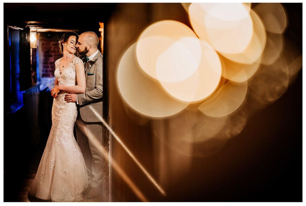 couple snuggling in a hallway with bokeh and lights