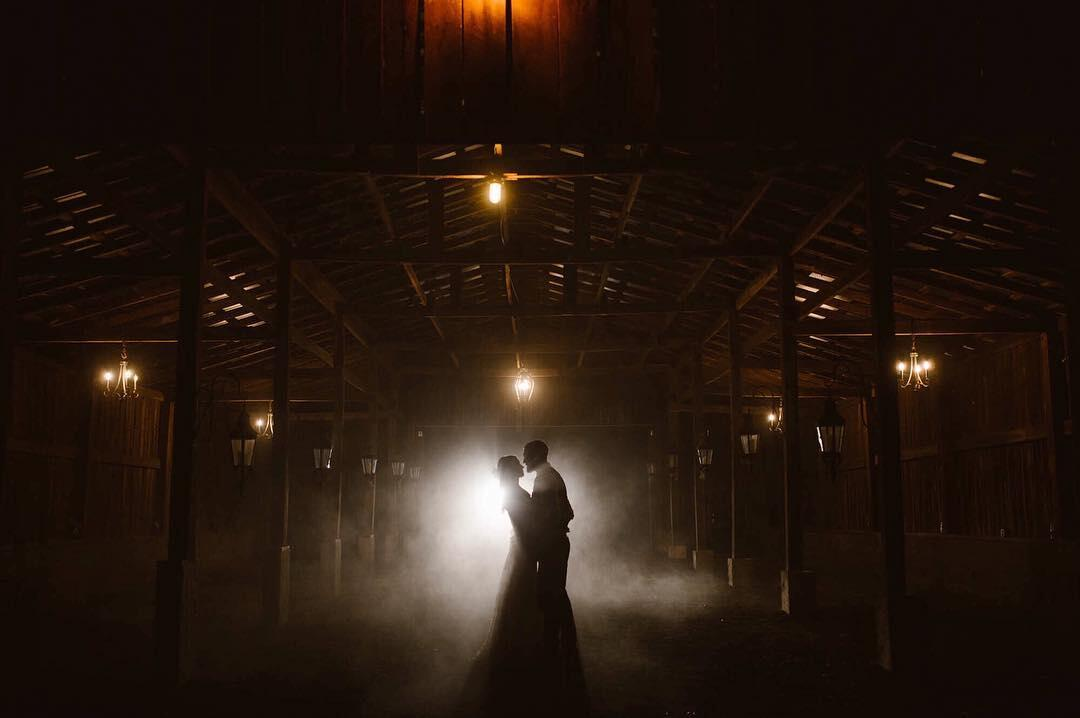 couple silhouetted in fog and lights