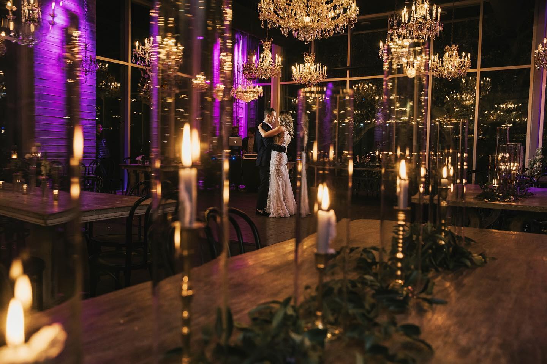 couple dancing on dance floor under chandeliers with city view