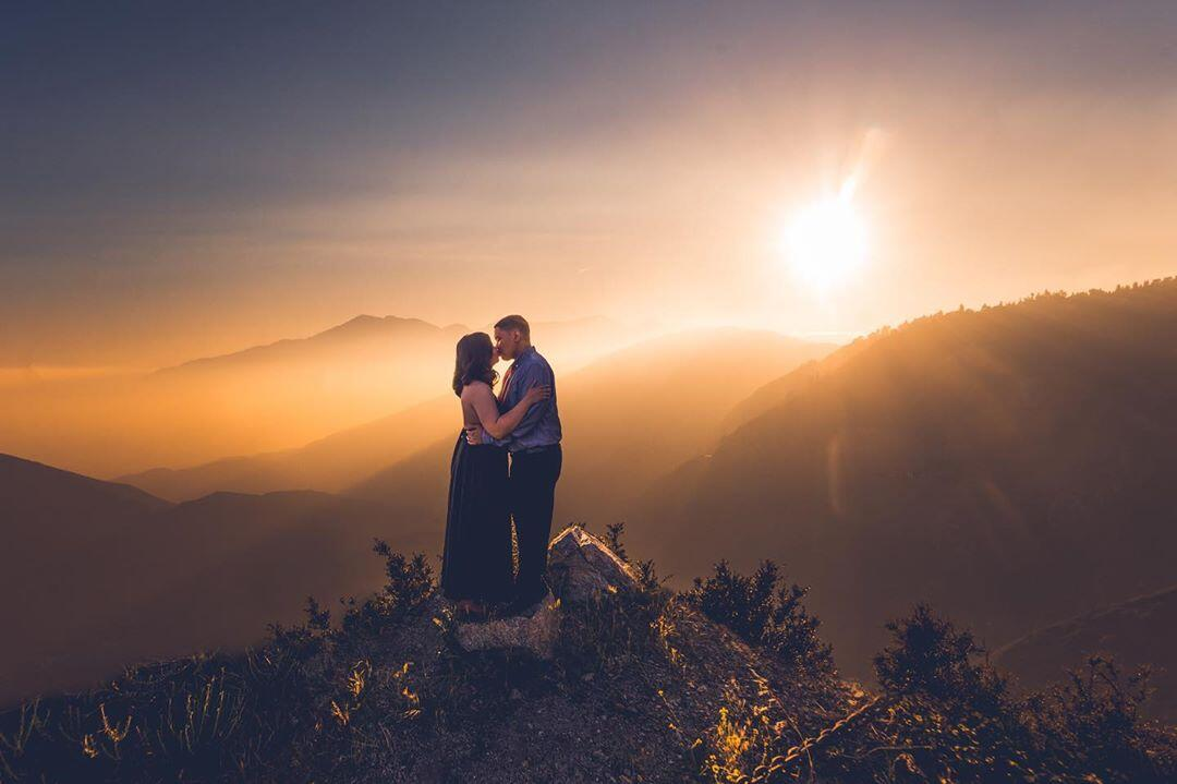 couple on top of a mountain at sunset kissing