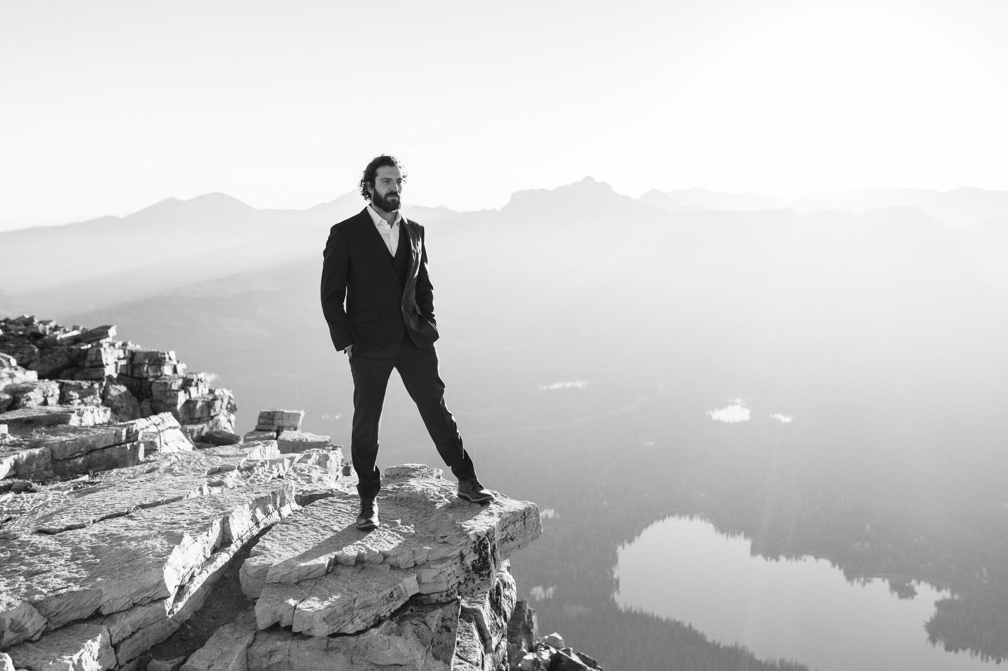 black and white image of man with beard standing on top of a mountain wearing a tux