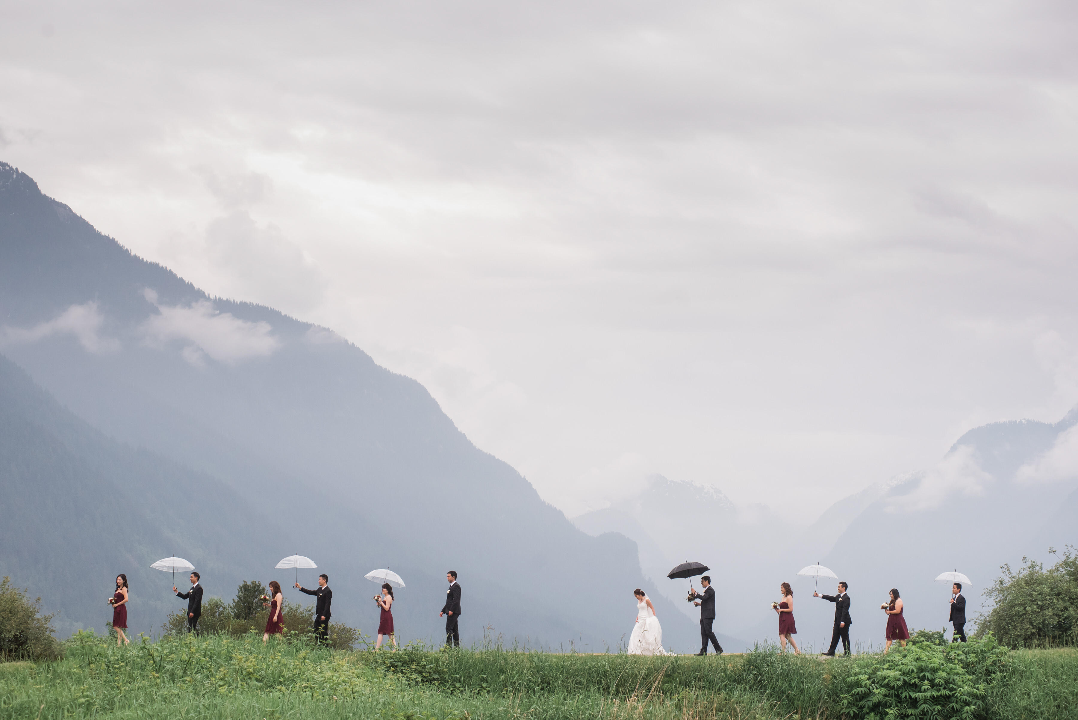 bridal party walking with bride and groom in the rain holding umbrellas