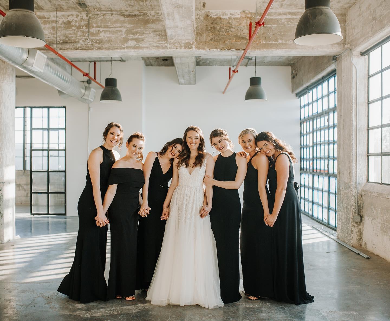 bridesmaids standing with bride hugging indoors