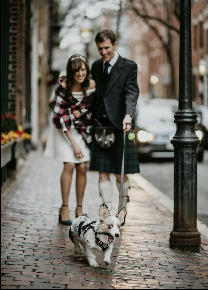 man wearing a kilt and woman wearing a dress with a checkered plaid walking a corgie