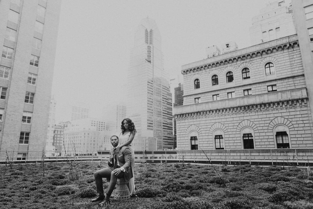 black and white photo of a couple standing on the top of a building with other buildings behind them
