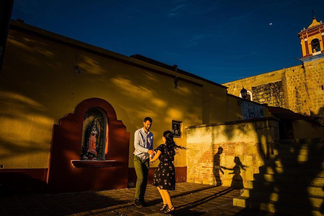 couple dancing in a square at sunset with their shadows in the background