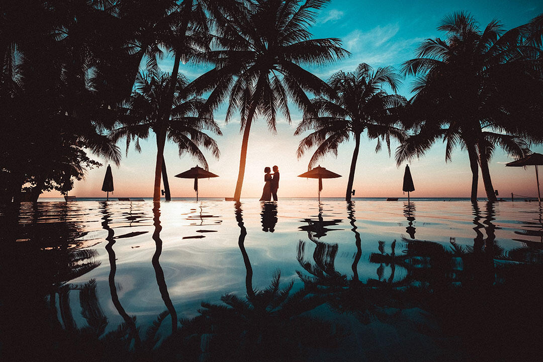 silhouette of couple embracing with palm trees, reflection in water and umbrellas