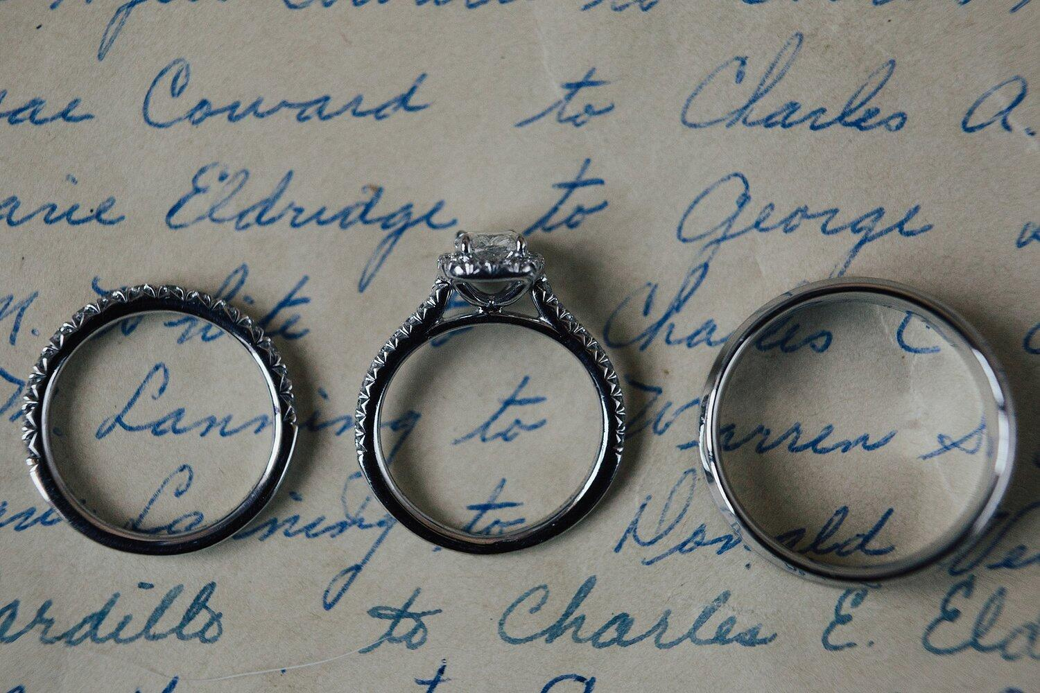 A set of 3 wedding rings placed on top of a handwritten letter