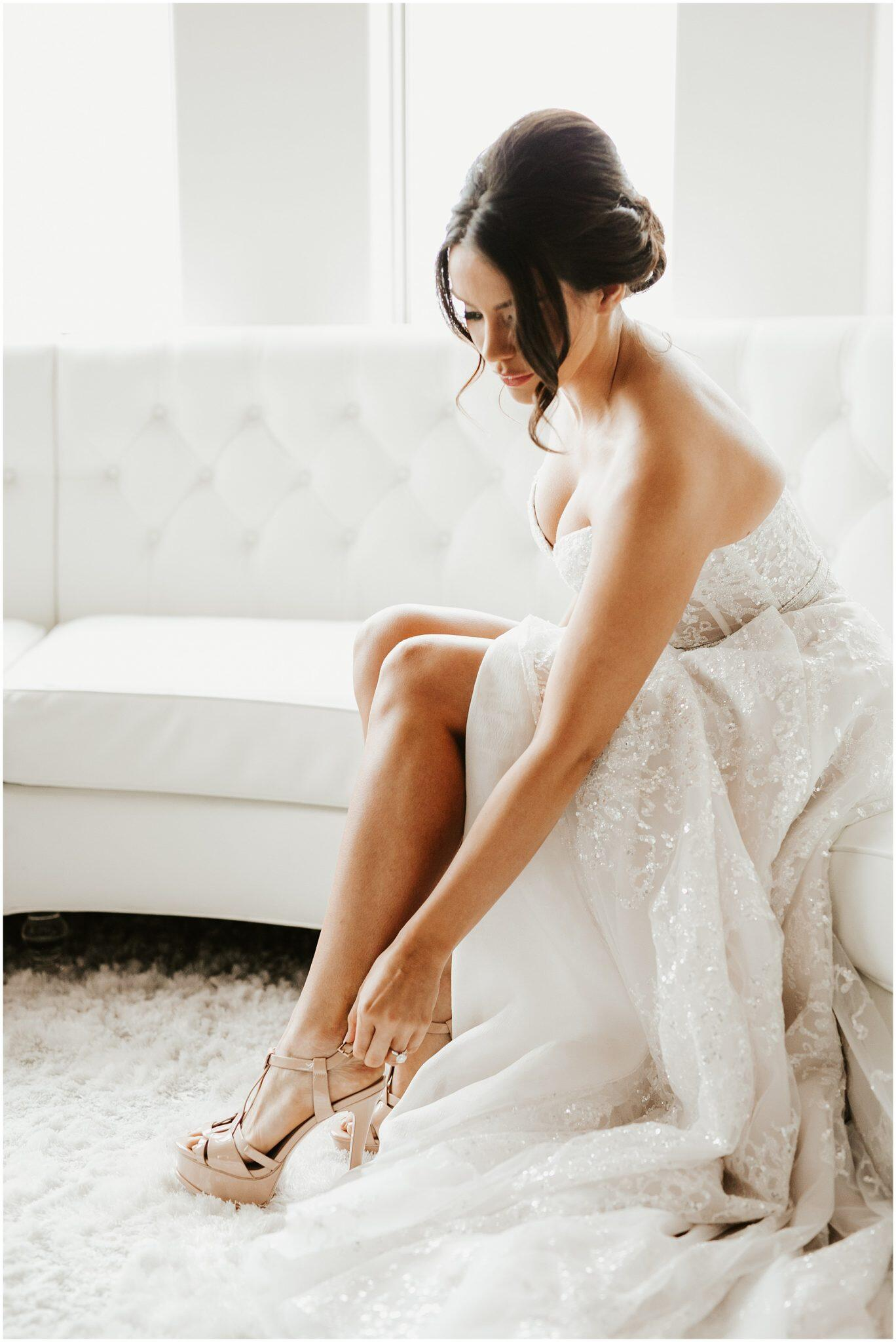 Portrait of a bride getting ready and wearing her shoe