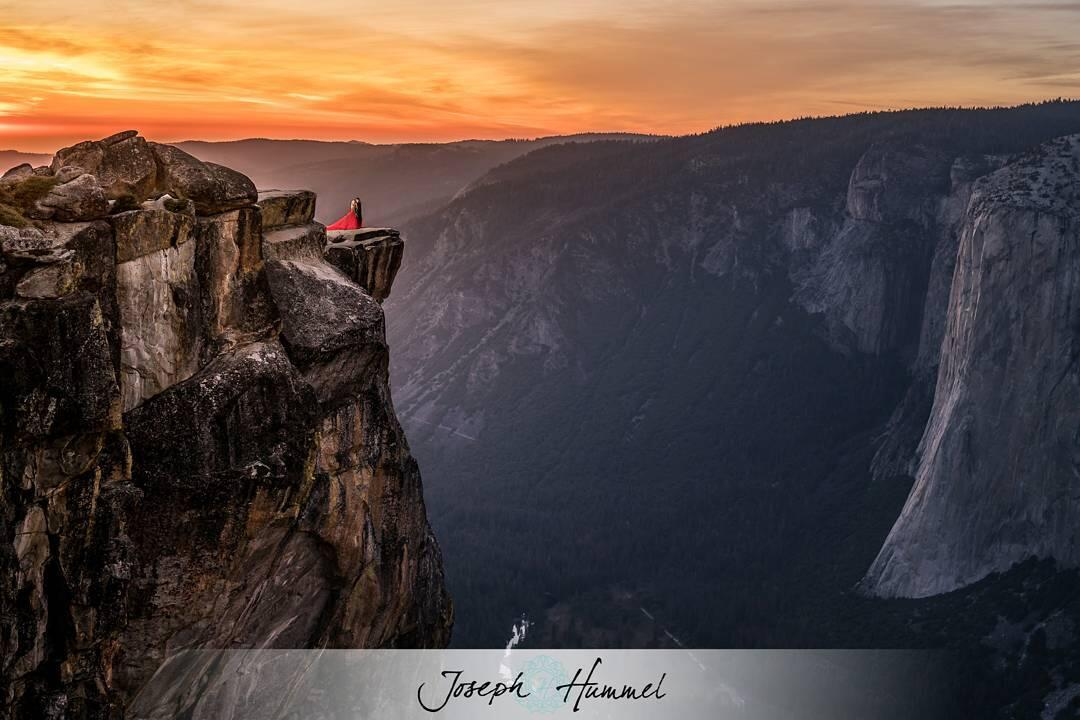 Adventure elopement photography featuring a couple posing on top of a cliff with a sunset sky backdrop