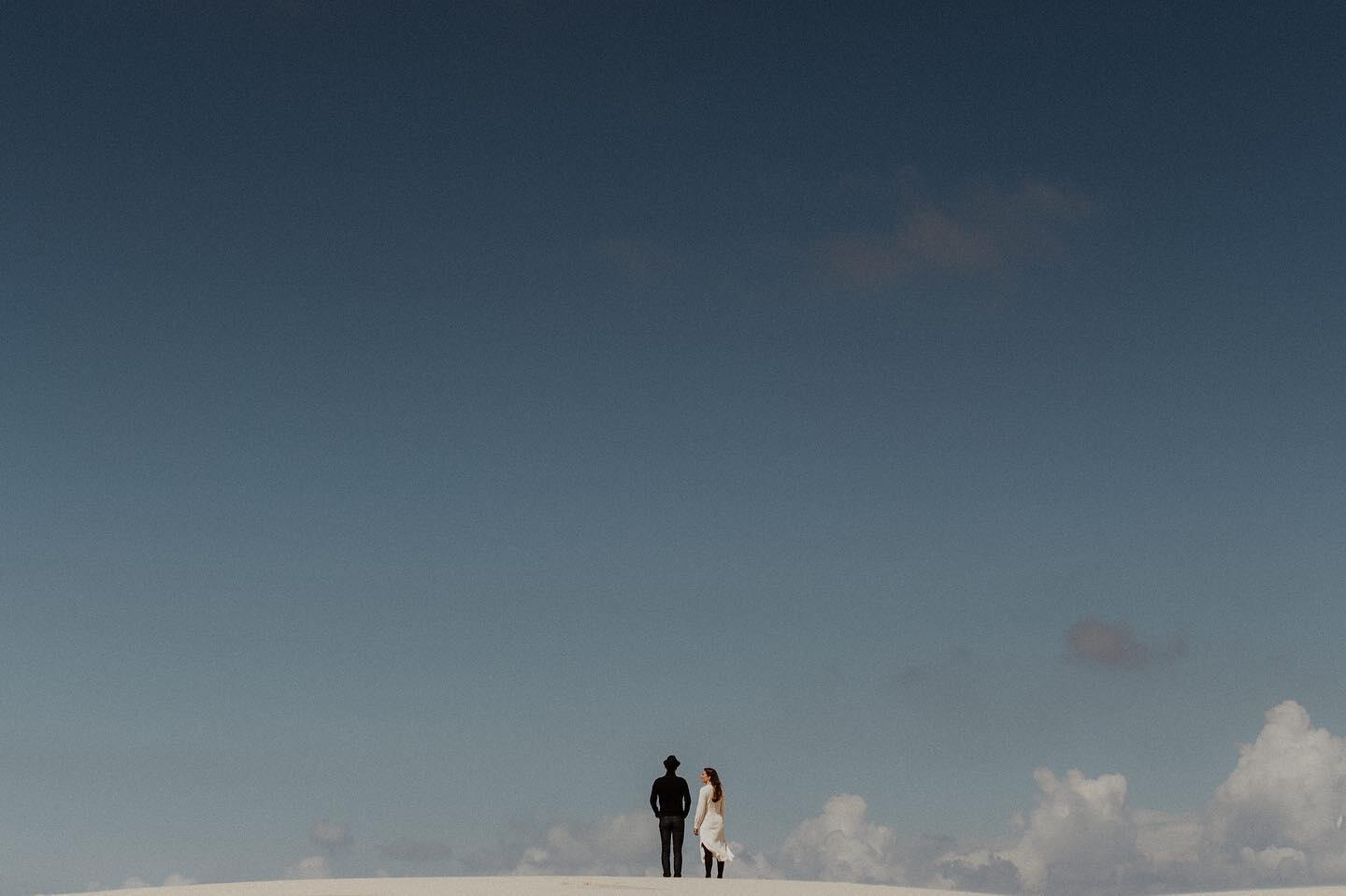 A couple posing with the sky as a backdrop