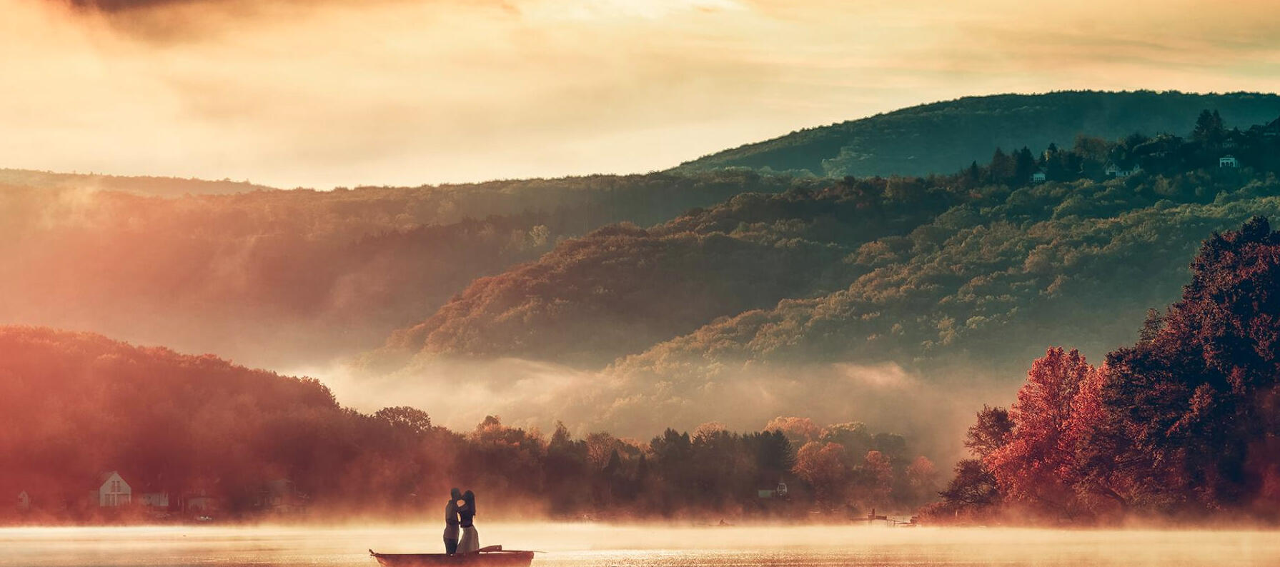 A couple posing on a boat in front of a hillside landscape colorfully lit by sun rays