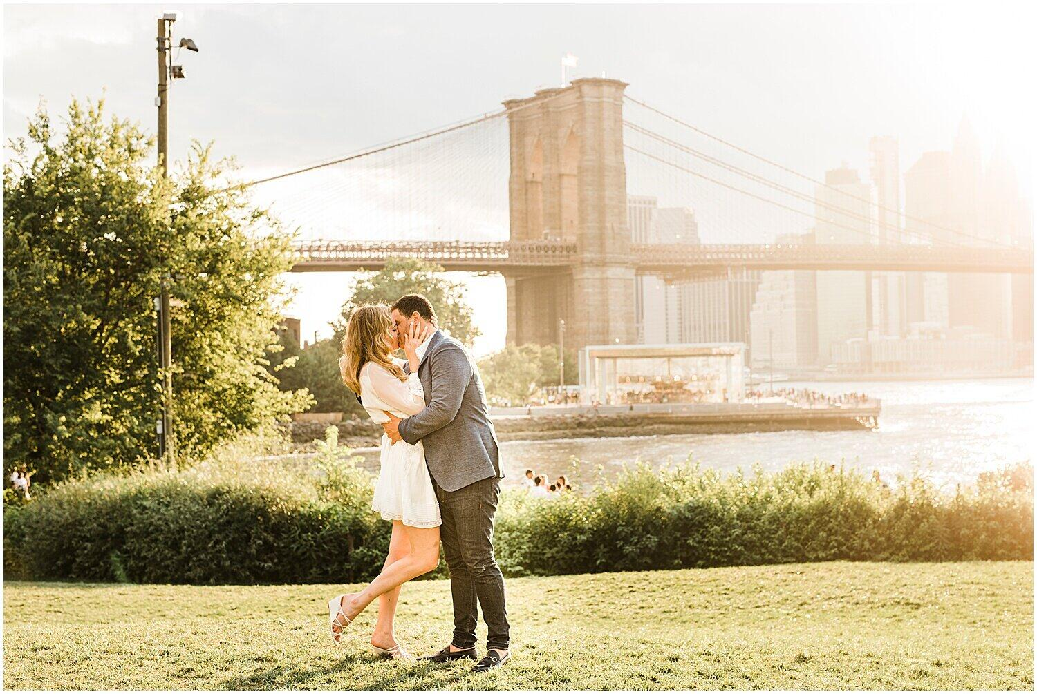 An engagement session photograph of a couple kissing with a bridge as a backdrop.