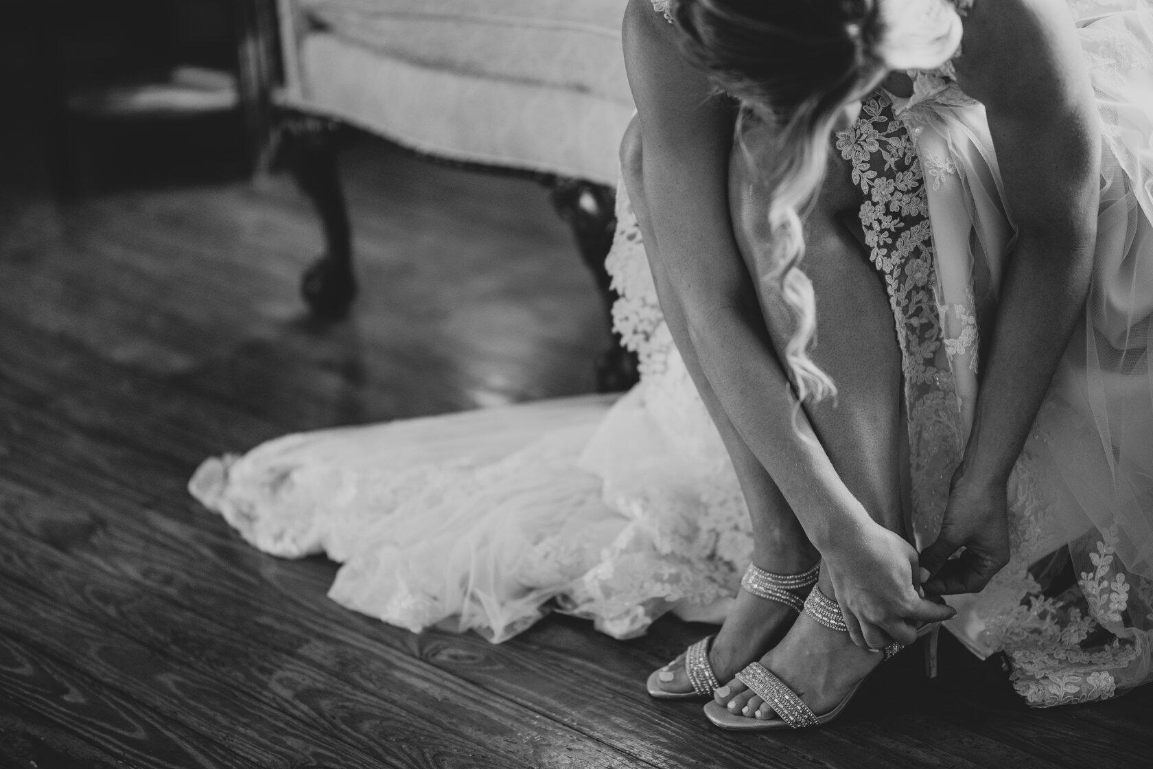 Black & white image of a bride kneeling down to buckle her shoe