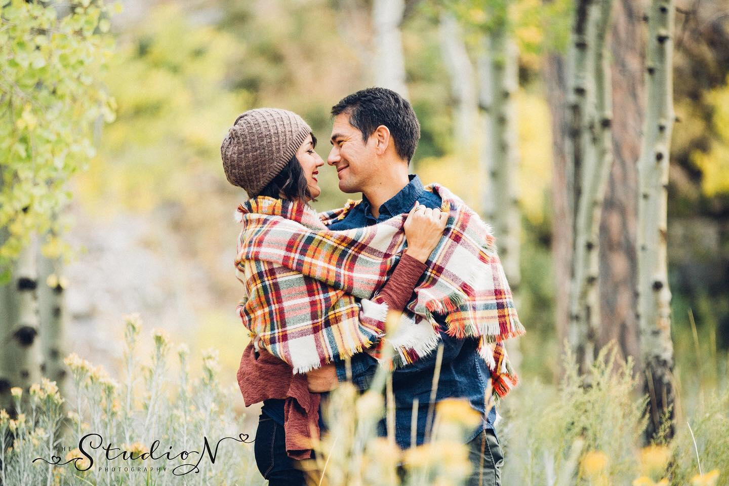 A couple holding each other while being covered by a scarf during a winter engagement session