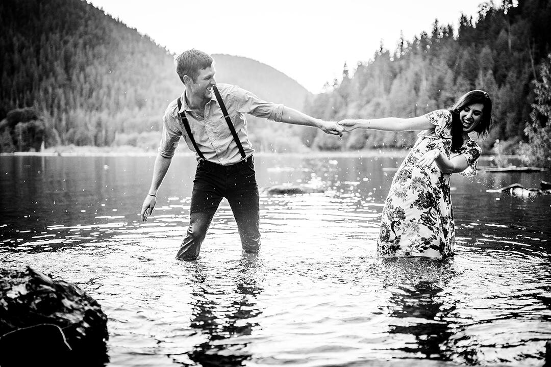 Black and white photo of a couple holding hands & splashing water at each other while standing knee-dipped in the lake
