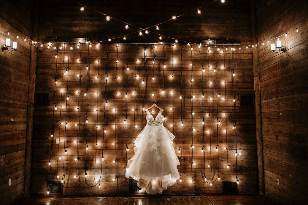 A bridal gown showcased in front of a wall with a fairy lights decoration.