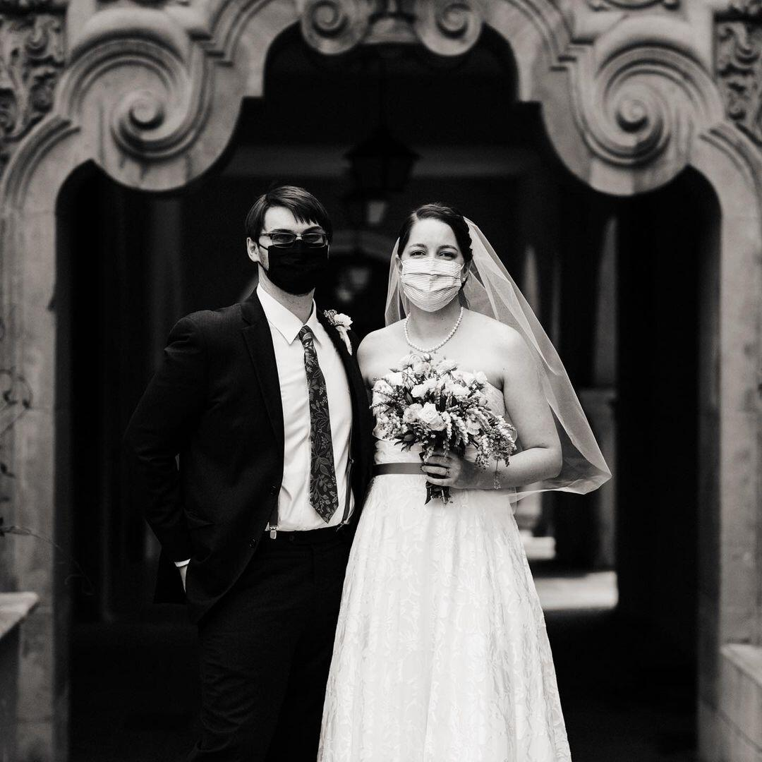 black and white photo of couple wearing masks in their wedding photo to protect against COVID