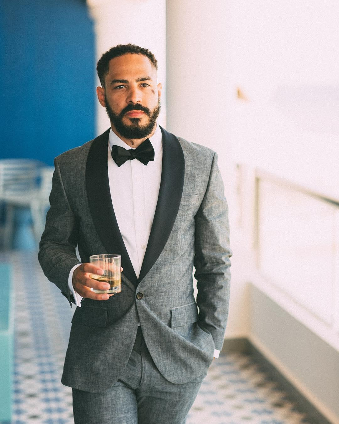 Portrait of a groom wearing a tuxedo walking with a glass in one hand.